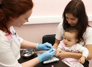 врач берет у ребенка кровь из пальца