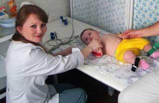 врач делает ЭКГ ребенку