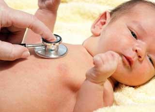 врач слушает сердце у новорожденного