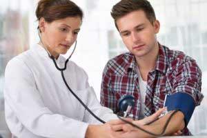 врач измеряет давление у молодого человека